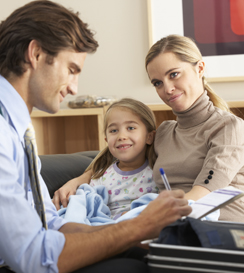 Doctor visiting sick child and mother at home